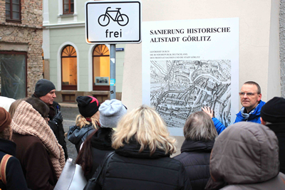 People on a guided city tour, view of the board with information on the renovation of the old town in Görlitz